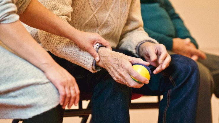 Photo shows the knees and some of the bodies and arms of three people.  The hands of the middle person look elderly and one hand holds a yellow ball the size of a tennis ball.  The person to their left has younger hands and holds the wrist of the ball holding hand in a caring way.