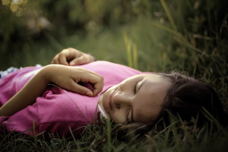 Close up of girls lying in green grass. She has her eyes closed and her hands rest on her chest and stomach in a relaxed manner. She is wearing a pink tshirt.