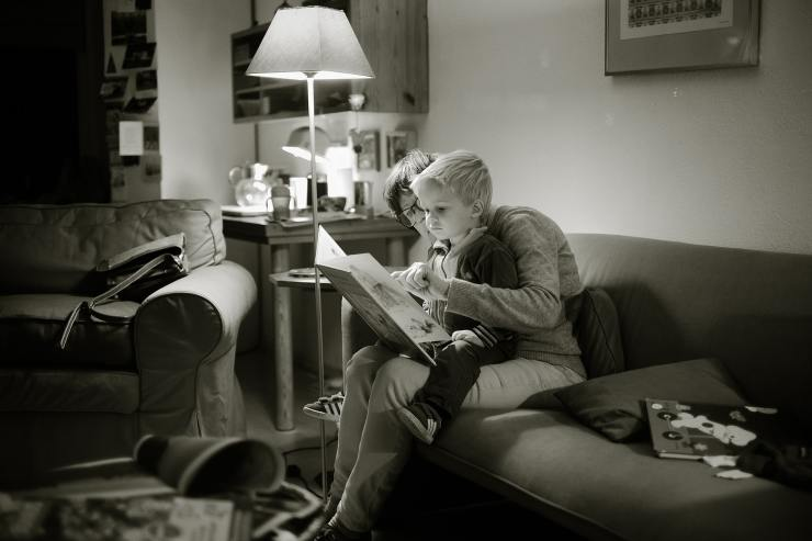 Black and white photo of lady sitting on a couch with a toddler boy sitting on her lap.  They are reading a picture book together.  A standard lamp illuminates the room