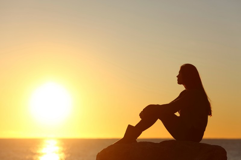Woman silhouette watching sun in a sunset