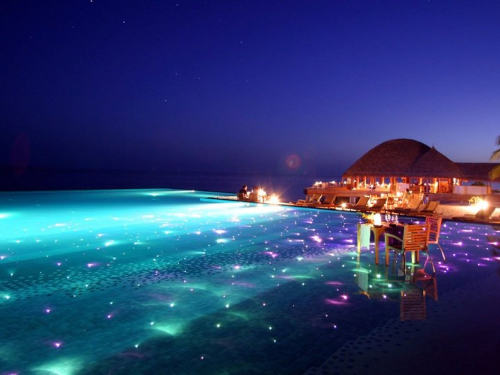 maldives-resort-huvafen-fushi-is-set-up-for-gorgeous-evening-swims-with-colored-lights-twinkling-beneath-the-surface