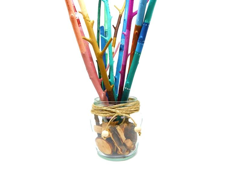 Centro de mesa hecho con un frasco de cristal y ramas secas pintadas de colores