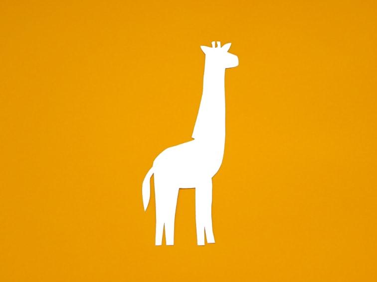 cartulina de color naranja claro y plantilla de una jirafa para hacer marcapaginas