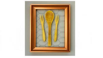 cuadro de cocina hecho con malla de gallinero y utensilios de cocina de madera