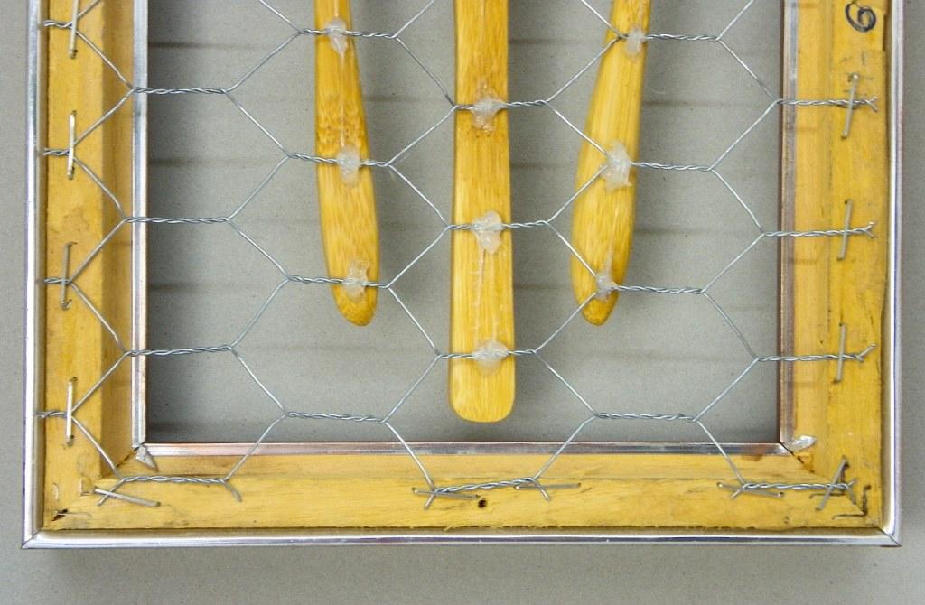 marco de madera con malla de gallinero grapada y utensilios de cocina pegados con silicona caliente