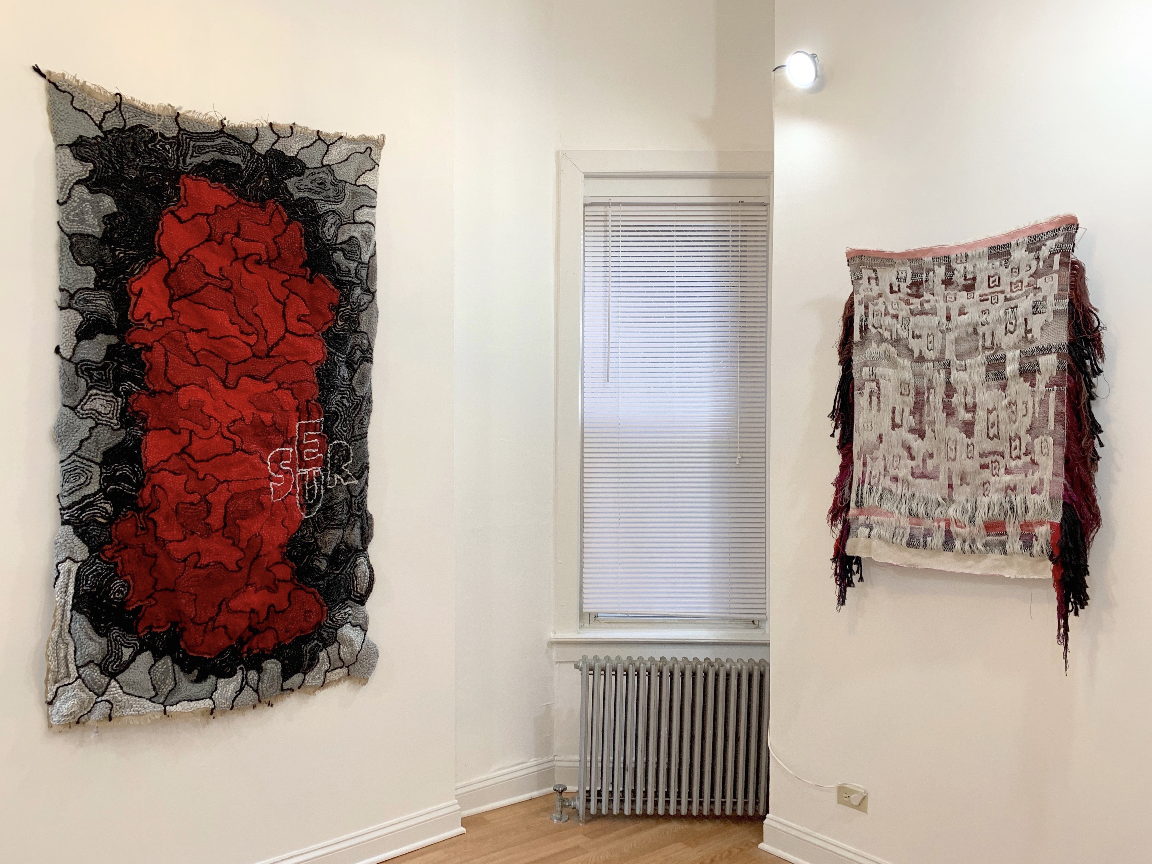 2 textiles artworks hanging on adjacent walls.
