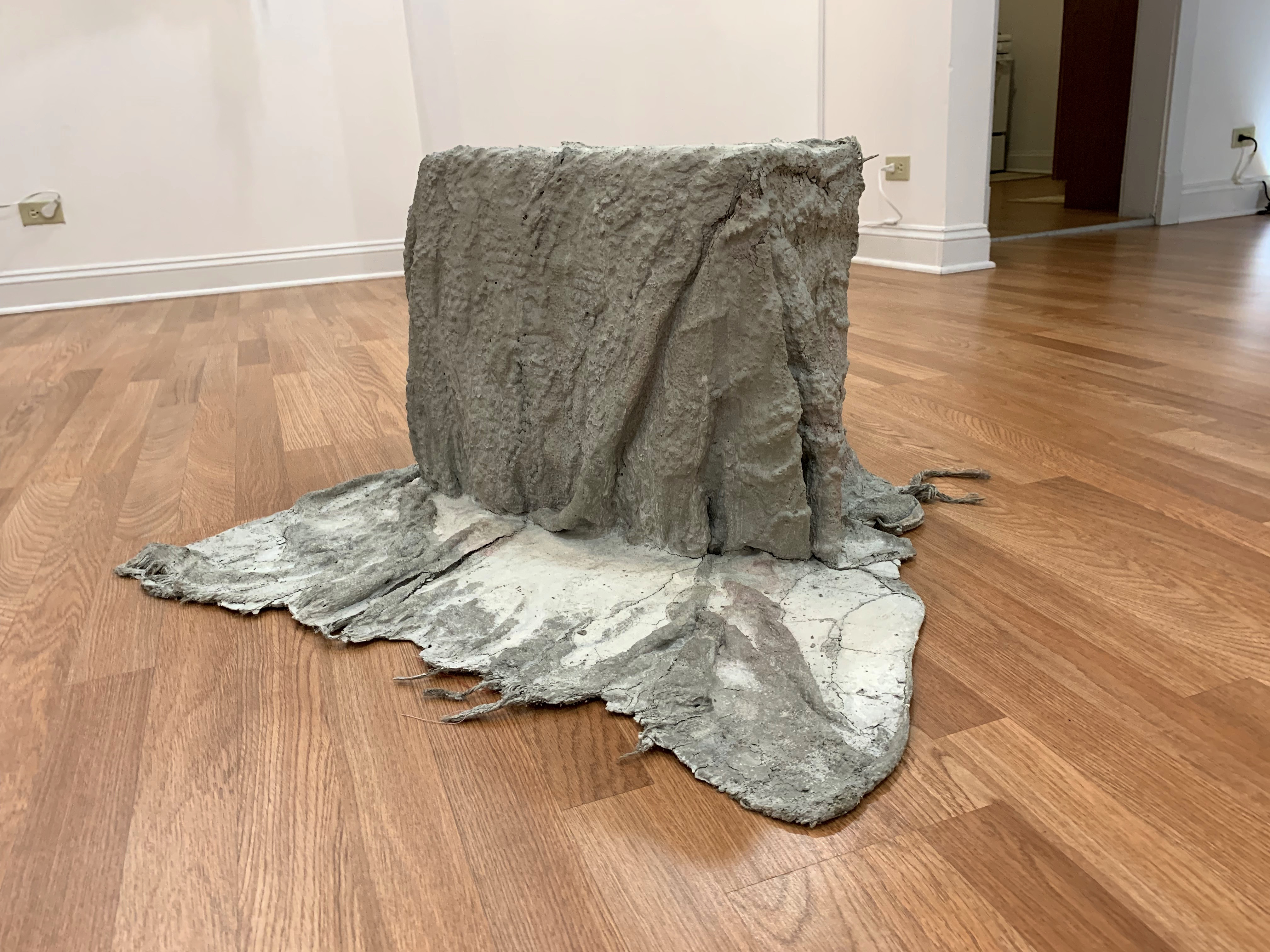 A grey textile artwork shaped in a box-like form sitting on the ground.