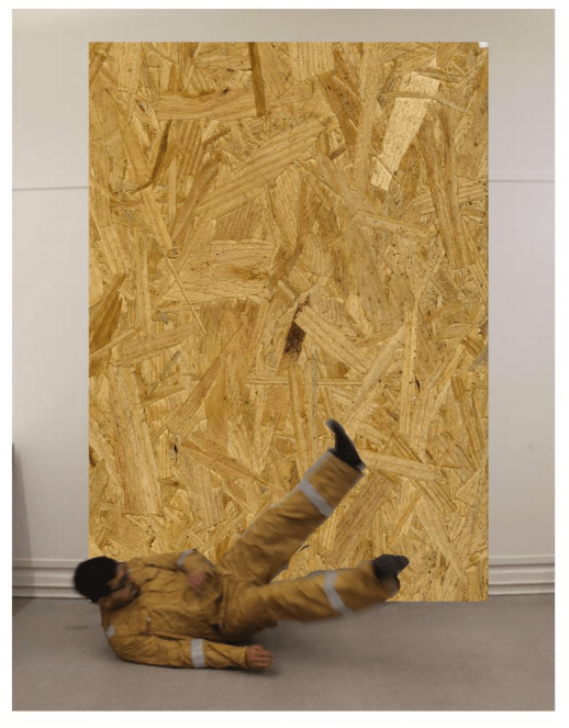 A photo of the artist wearing a yellow-wood color jumpsuit falling in front of a wooden board with the same color.