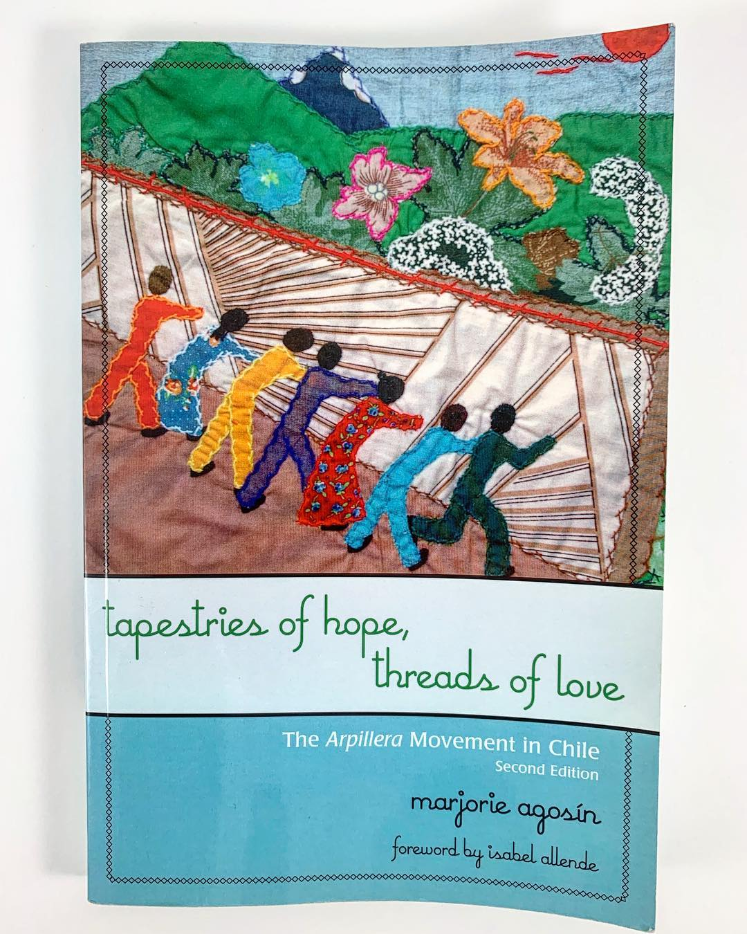 Book cover of a textile with human likes figures in front of a wall-like structure in front of a mountain landscape.