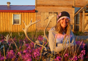 Summer guest Katlin Miller in flowers at Seal River Heritage Lodge.