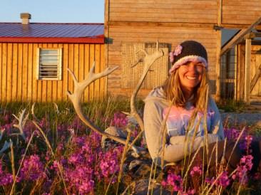 Summer guest Katlin Miller in flowers at Seal River Heritage Lodge.