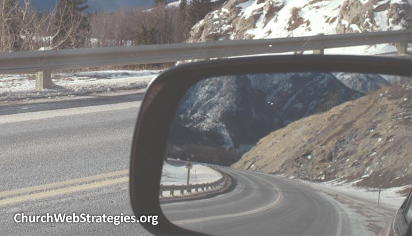 car side mirror showing road behind it