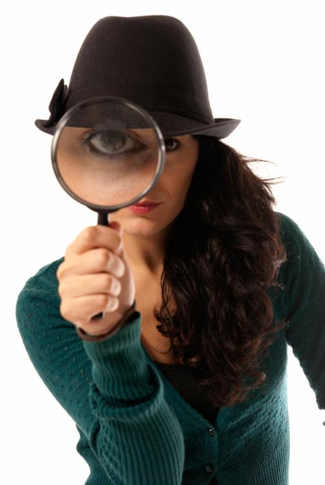 woman looking through magnifying glass loupe detective isolated