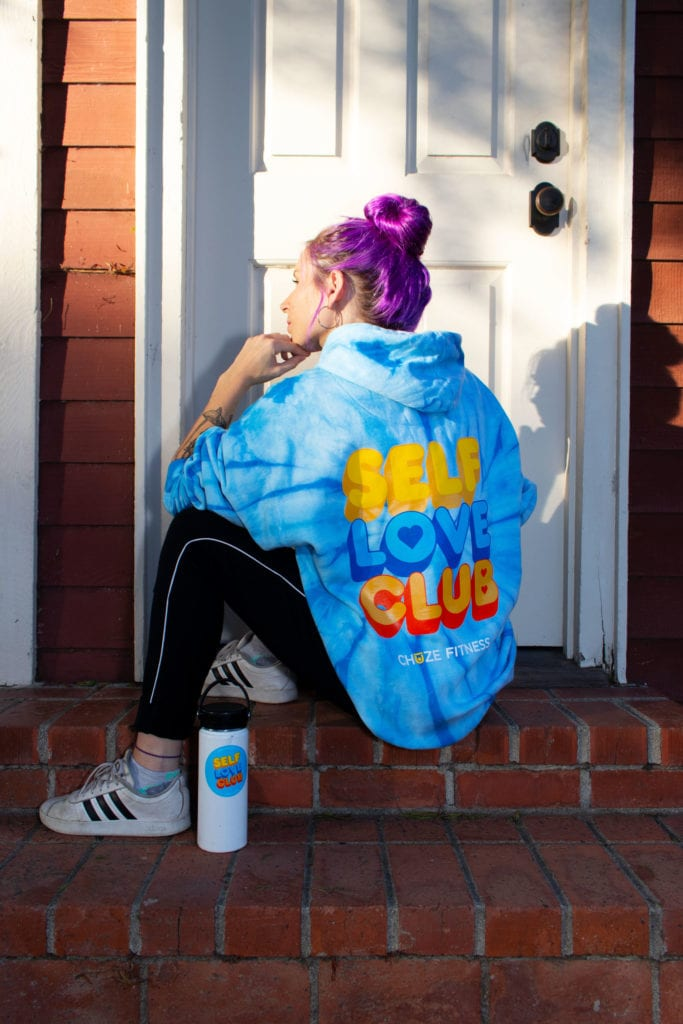 "Woman in sitting in front of a doorway with our blue ""Self Love Club"" hoodie and a water bottle covered in our Self-Care Sticker Pack"