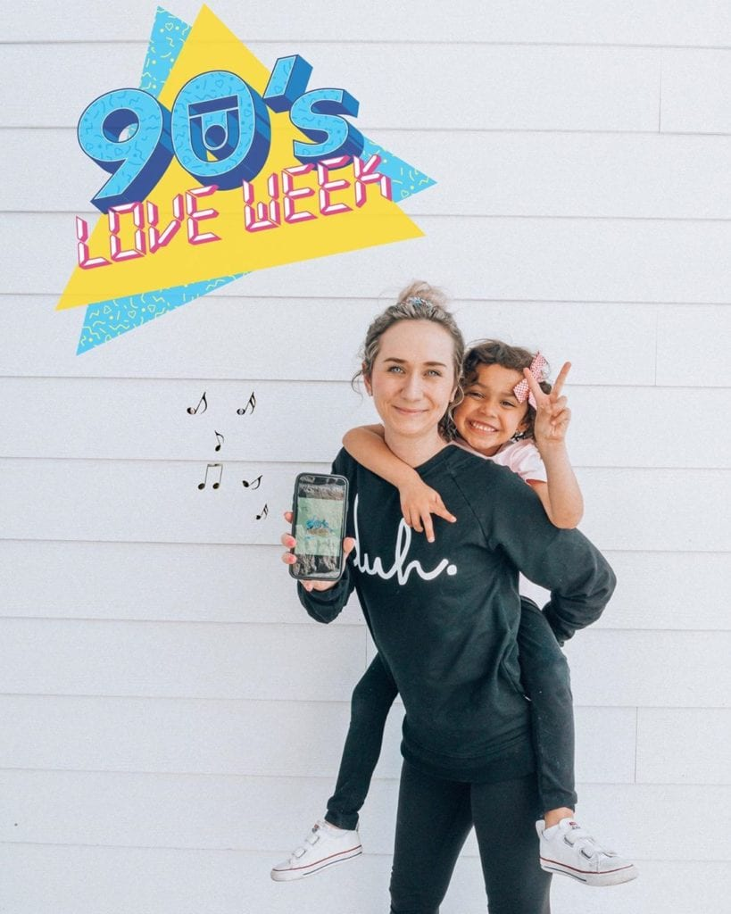 Aly and her daughter posing in front of a white wall with the 90's Love Week logo overhead