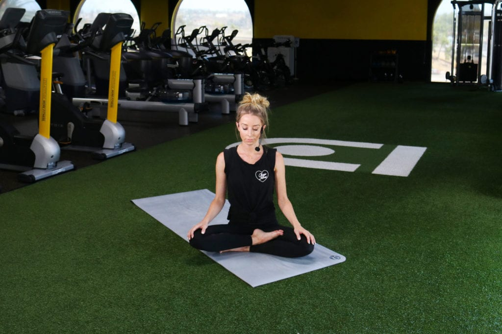 A woman practicing meditation on the Chuze Fitness Turf area for self-care