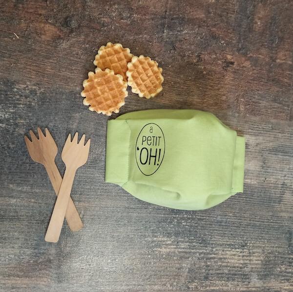 mascarilla infantil verde personalizada al lado de unos cubiertos de madera y 3 gofres mini
