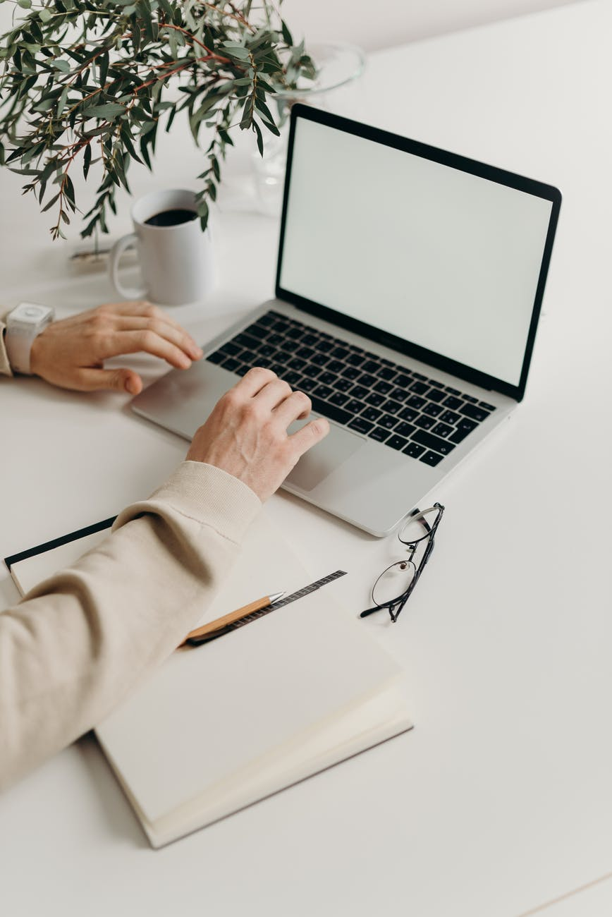 person using macbook pro on white table
