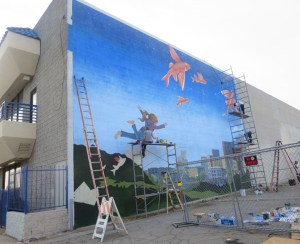 Artists adding the finishing touches on a mural for CicLAvia