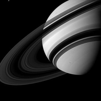 In alto a sinistra vedete la luna Teti, uno dei satelliti naturali di Saturno