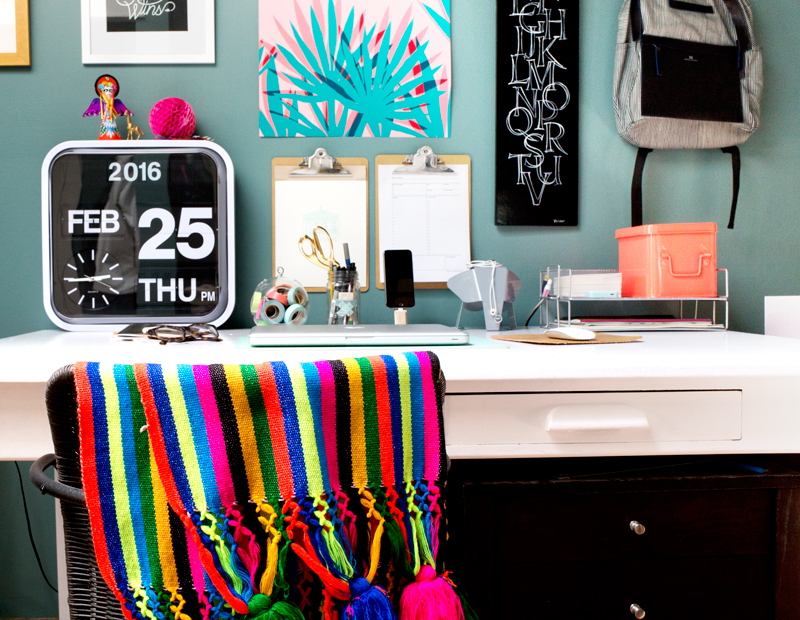 Add pops of brights to your home office, like a striped blanket and unique art prints!