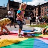 Zdjęcie przedstawiające dzieci podczas zabawy z kolorową chustą