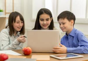 School girls and boy playing on laptop in school