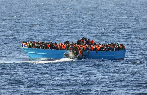 A crowded boat with migrants awaits rescue by EU NAVFOR MED.