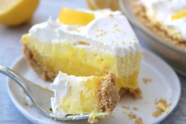 Fork filled with lemon pie on plate.