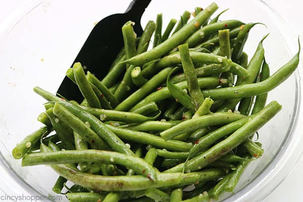 Tossing garlic green beans in a bowl.