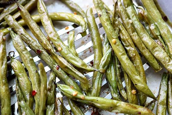 Crispy roasted green beans on a spatula.