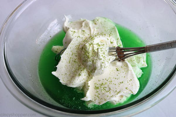 Adding whipping cream and lime zest to lime Jello for lime cheesecake.