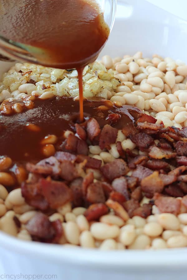 Adding sauce to baked beans.