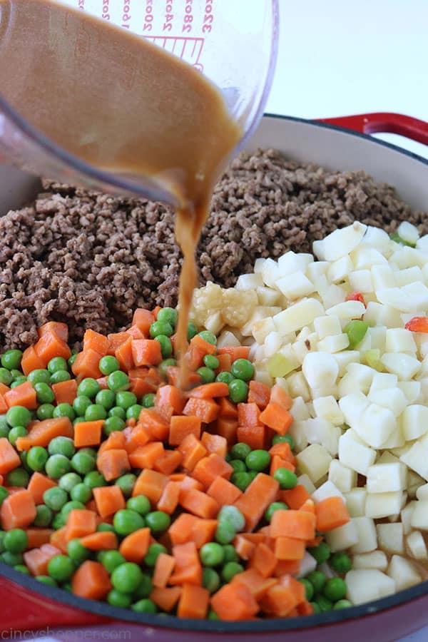 Adding gravy to ground beef dinner skillet.