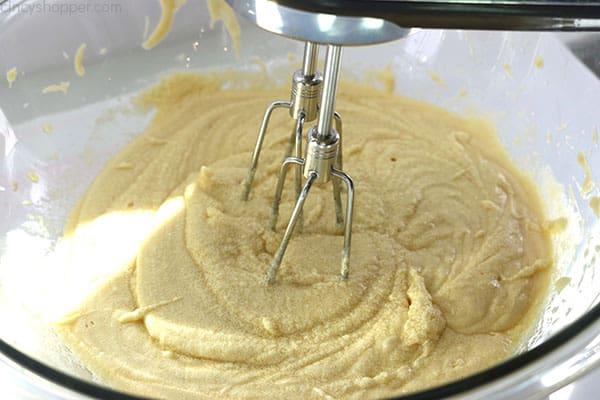 Mixing banana cake ingredients in a bowl.