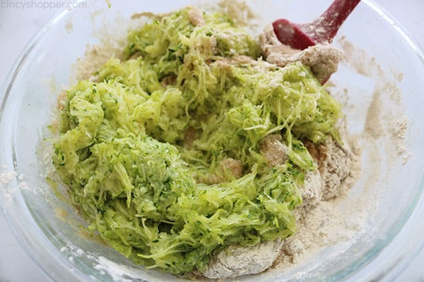 Adding shredded zucchini to mixture.