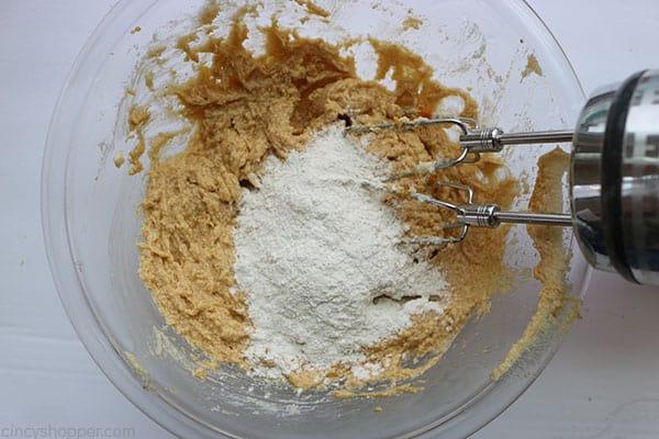 Adding flour mixture to pumpkin cookie dough.