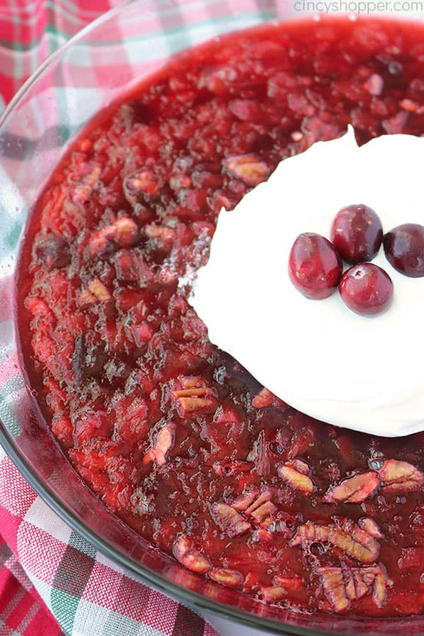 Old Fashioned Cranberry Salad in a clear bowl with whipped cream and fresh cranberries.