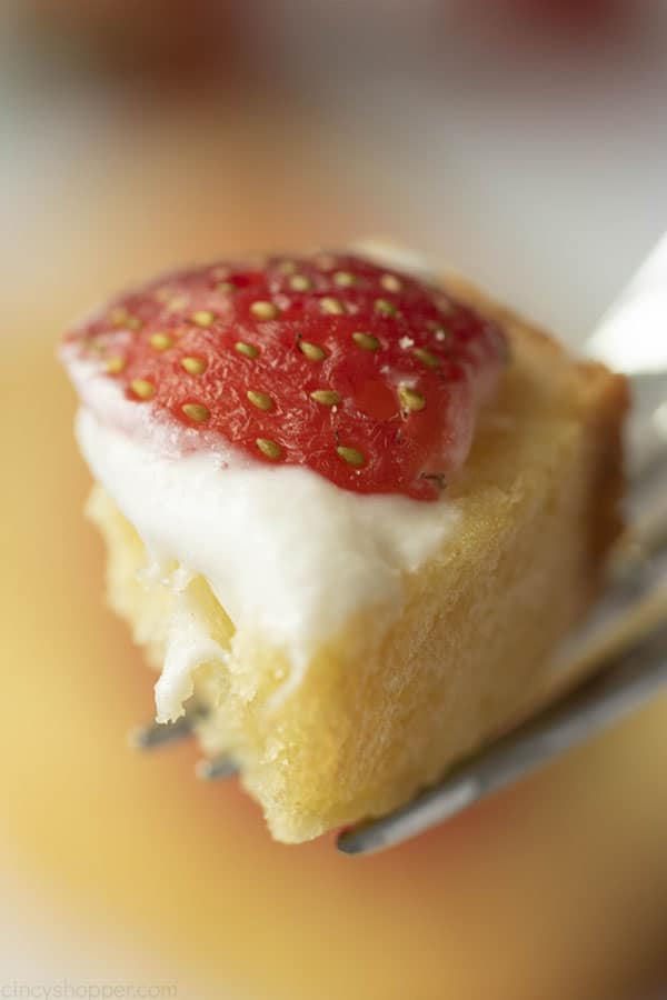 close up of a bite of moist pound cake recipe on a fork with whipped cream and strawberry