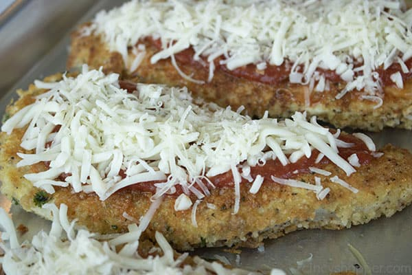 topping chicken Parmesan with shredded Mozzarella cheese