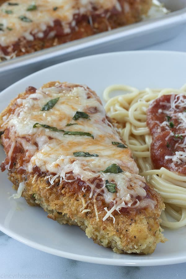 breaded chicken breast smothered with cheese next to spaghetti
