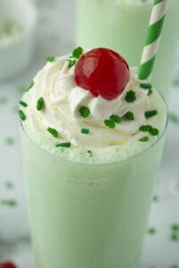 tall glass with thick green mint milkshake, whipped cream and cherry on top