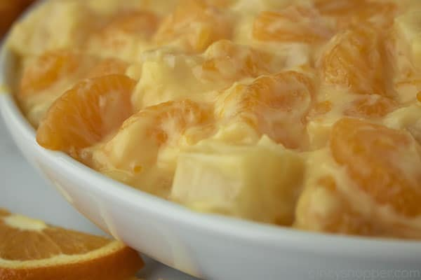 Creamy salad in a white bowl with oranges and pineapples