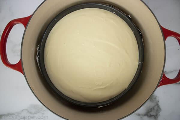 new york style cheesecake in a water bath inside a dutch oven