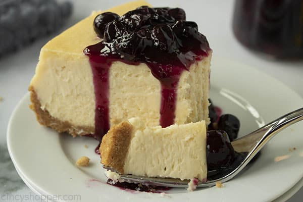 slice of creamy baked cheesecake on a plate covered in blueberry sauce