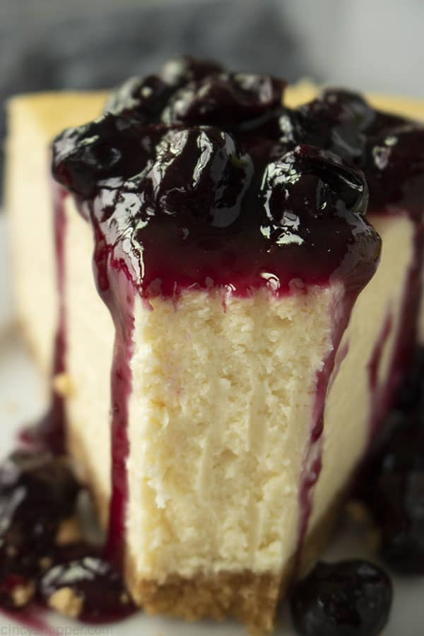 close up photo of creamy ny style cheesecake with blueberry sauce