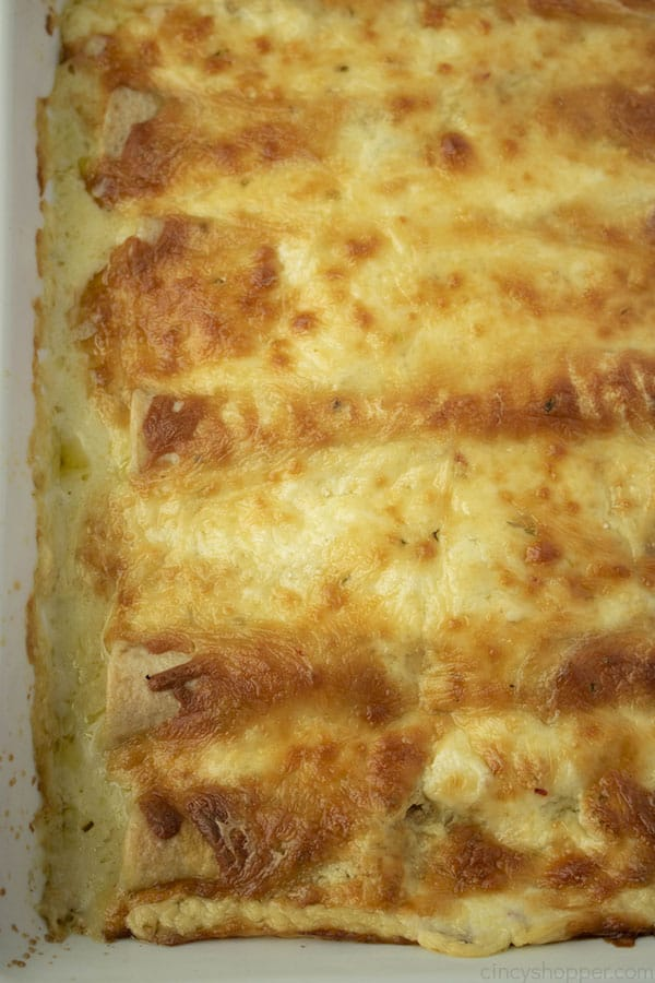 close up image of baked chicken enchiladas in casserole dish