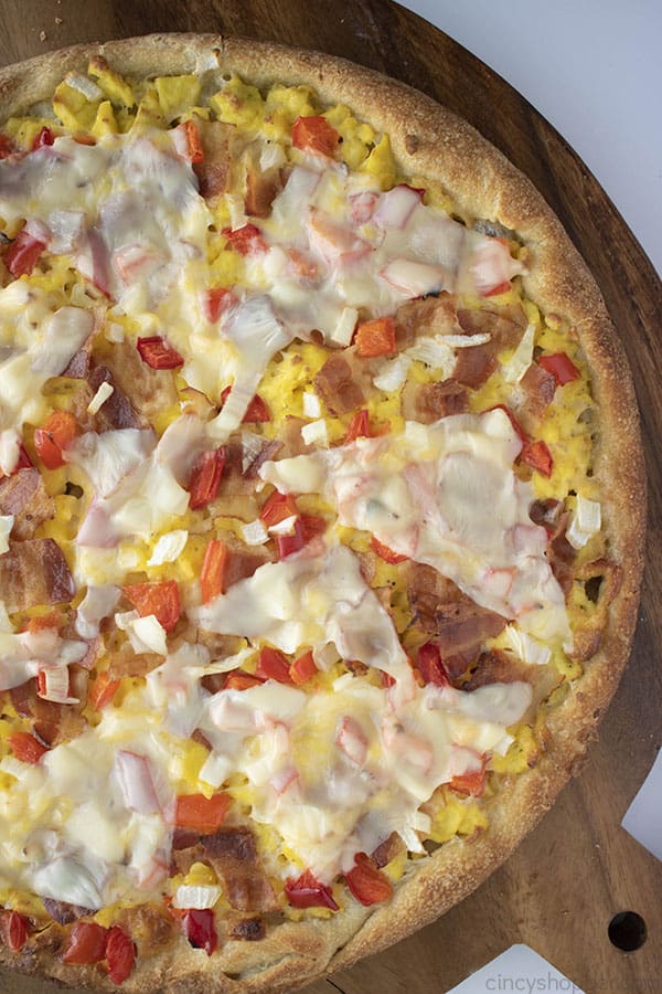 breakfast pizza with bacon, eggs, and cheese
