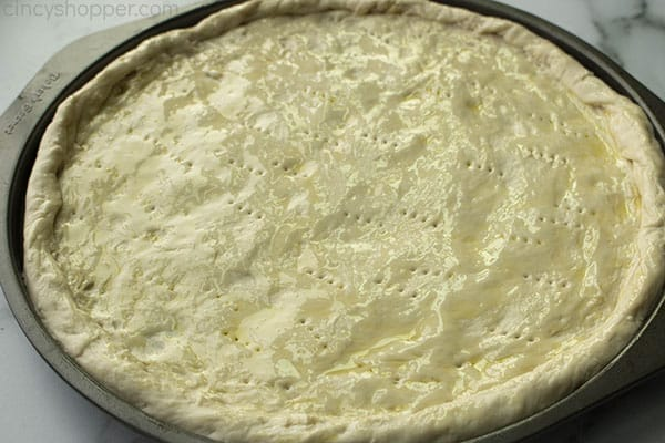 unbaked pizza dough on a circular pizza pan