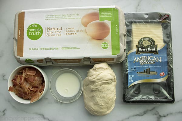 ingredients on counter to make a pizza recipe: pizza dough, bacon, eggs, and American cheese